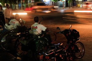 Yangon rickshaw men watch night traffic